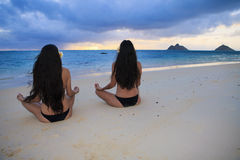 Mother and daughter meditating. Mother and daughter on the beach in hawaii at sunrise doing yoga and meditation Stock Photos