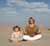 Mother and daughter meditating. In desert Stock Photography