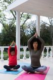 Mother and daughter meditating together in the porch. At home Stock Photography