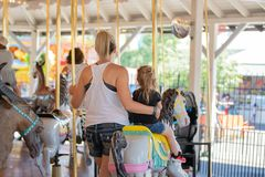 Mother and daughter on merry-go-round stock photography