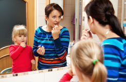 Mother and daughter with mirror. Mother and little daughter playing before the mirror in bathroom Royalty Free Stock Images