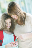 Mother and daughter with mobile phone. Mother and daughter smiling with mobile phone Stock Photography