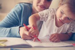 Mother and daughter at home. Mother teaching her daughter to drawing and writing. Mother and daughter . Mother teaching her daughter to drawing and writing royalty free stock images