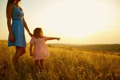 Mother and daughter in nature at sunset. Stock Image
