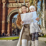 Mother and daughter near Arc de Triomf in Barcelona with map. In Barcelona for a perfect winter. Portrait of happy trendy mother and daughter near Arc de Triomf Royalty Free Stock Photography