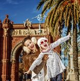 Mother and daughter near Arc de Triomf having fun time. In Barcelona for a perfect winter. Portrait of smiling trendy mother and daughter near Arc de Triomf in Stock Photography