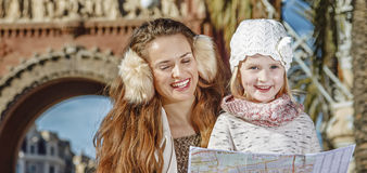 Mother and daughter near Arc de Triomf looking at map. In Barcelona for a perfect winter. smiling modern mother and daughter near Arc de Triomf in Barcelona Royalty Free Stock Photo