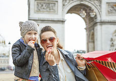 Mother and daughter near Arc de Triomphe eating macaroons Stock Photos