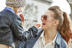 Mother and daughter near Arc de Triomphe eating macaroons Stock Photo