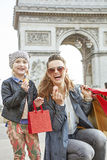 Mother and daughter near Arc de Triomphe showing macaroons Stock Photo