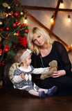 Mother and daughter near Christmas tree Stock Images