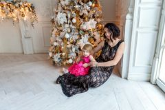 Mother and daughter near a Christmas tree Stock Photos