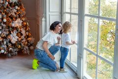 Mother and daughter near a Christmas tree Royalty Free Stock Photography