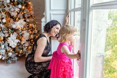 Mother and daughter near a Christmas tree Royalty Free Stock Photo