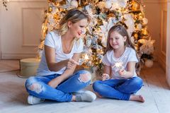Mother and daughter near a Christmas tree Stock Image