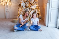 Mother and daughter near a Christmas tree Royalty Free Stock Photos