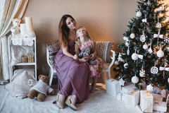 Mother and daughter near the Christmas tree, hugging, preparation for Christmas, decoration, decor, lifestyle, family, family valu Stock Photo