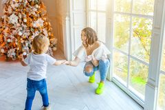 Mother and daughter near large window and Christmas tree at home royalty free stock photo