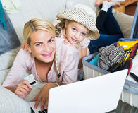 Mother with daughter near suitcase with credit card. Happy european mother with little daughter near suitcase with credit card and notebook Stock Photo