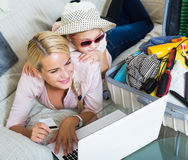 Mother with daughter near suitcase with credit card. Happy russian mother with little daughter near suitcase with credit card and notebook Royalty Free Stock Images