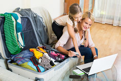 Mother with daughter near suitcase with credit card. Smilin american mother with little daughter near suitcase with credit card and notebook Stock Photos