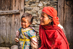 Mother and daughter in Nepal. Beni, Nepal - circa May 2012: Mother in red scarf and headcloth kneels near her small daughter with brown hair and brown eyes in Royalty Free Stock Image