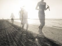 Mother and daughter next to the other running long the shoreline. Of an Italian beach in  the early morning Royalty Free Stock Images