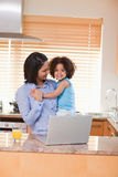 Mother and daughter with notebook in the kitchen Royalty Free Stock Image
