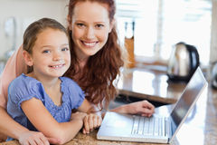 Mother and daughter with notebook in the kitchen Stock Images