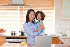 Mother and daughter with notebook in the kitchen together Stock Image