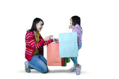 Mother and daughter opens shopping bags on studio Stock Image