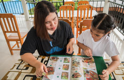 Mother and daughter are ordering from the menu. royalty free stock image