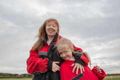 Mother and daughter outdoor and cloudy sky Stock Images