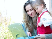 Mother and daughter outdoor with notebook Stock Photo
