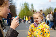 Mother with daughter outdoor. Playing and making soap bubbles. Beautiful young smiling women blowing bubbles to smiling little girl. Childhood and parenthood Royalty Free Stock Photos