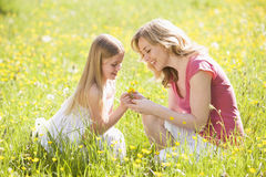 Mother and daughter outdoors holding flower Royalty Free Stock Images