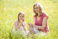 Mother and daughter outdoors holding flower Stock Photo