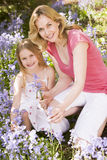 Mother and daughter outdoors holding flowers Stock Photography
