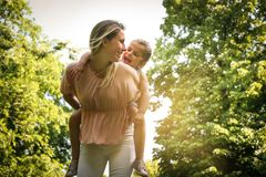 Mother and daughter outdoors in a meadow. Mother carrying her da royalty free stock photo