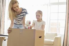 Mother and daughter packing cardboard box at home Royalty Free Stock Photography