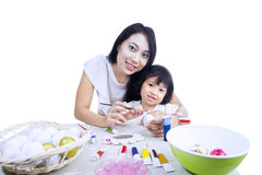 Mother and daughter paint easter eggs Stock Photography