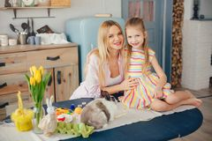 Mother with little daughter in a kitchen stock photos