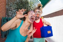 Mother and daughter with painted face making grin. Portrait of happy family, women and three years old child painted faces, looking smiling and making grin, in Royalty Free Stock Photo
