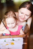Mother and daughter painting a batik Royalty Free Stock Images