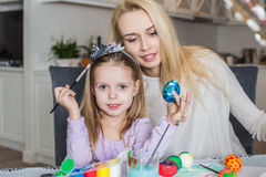 Mother And Daughter Painting Easter Eggs In Home Stock Photo
