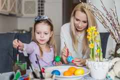Mother And Daughter Painting Easter Eggs In Home Stock Images