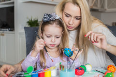 Mother And Daughter Painting Easter Eggs In Home Stock Photography