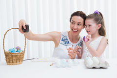 Mother and daughter painting easter eggs Stock Images