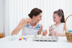 Mother and daughter painting easter eggs Stock Photos