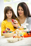 Mother and daughter painting eggs Royalty Free Stock Photos